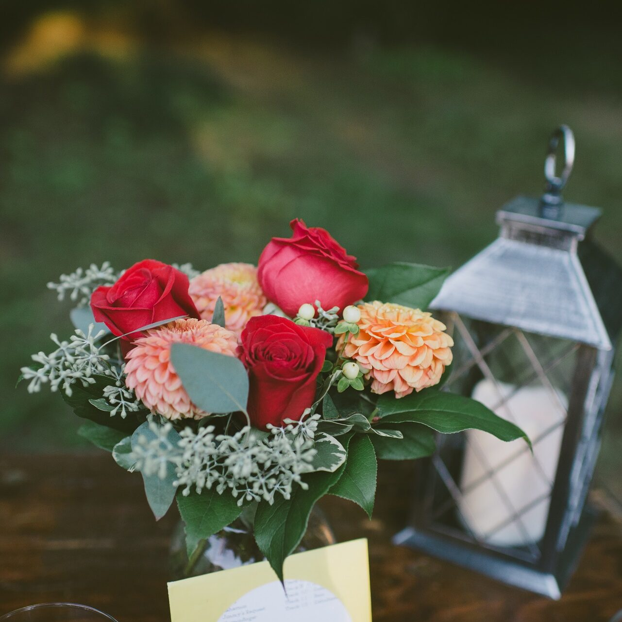 addon options for your wedding ceremony, elope in michigan, flowers and lantern on a table at a backyeard wedding by a saugatuck wedding planner, micro wedding packages